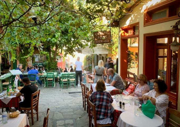 Diners eat at outdoor tables at a Greek taverna