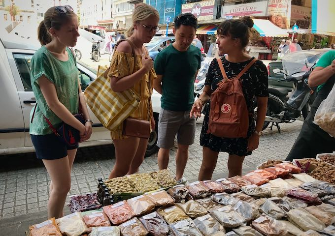 A tour guide shows spices at a farmers market to a group of tourists
