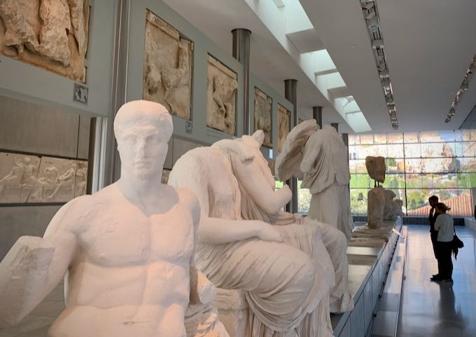 Two people study ancient Greek sculpture in a museum.