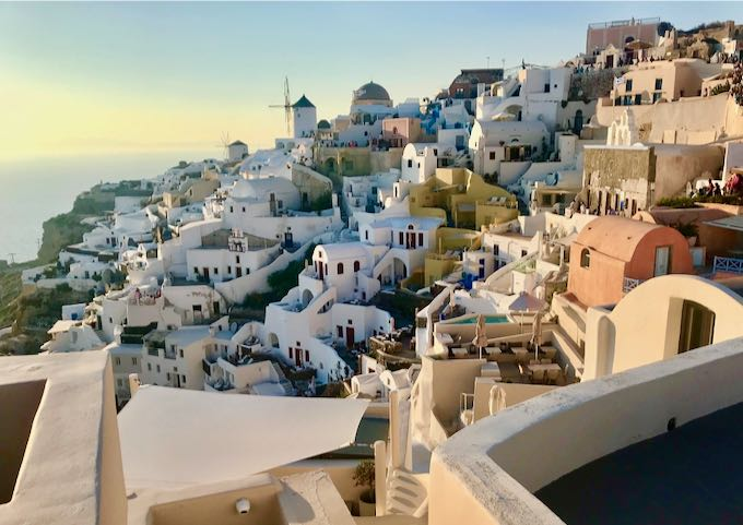 Cliffside cave hotels in Oia Village, Santorini, at sunset