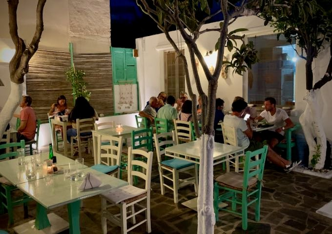 Diners at outdoor tables in a Greek taverna at night