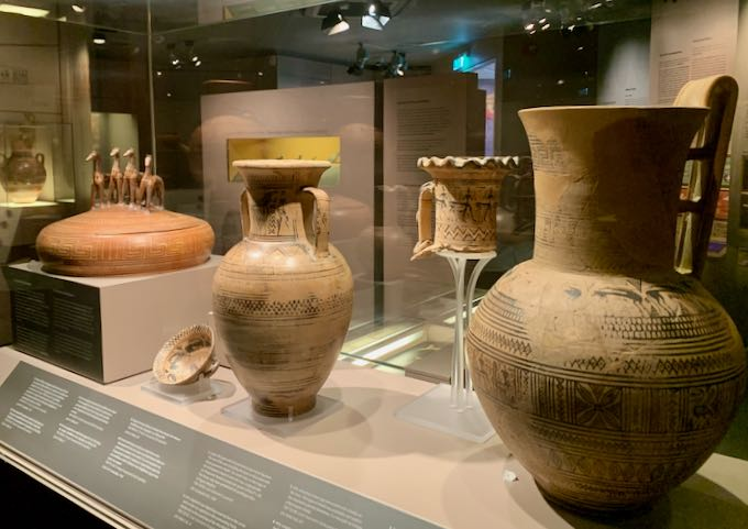 Ancient pottery on display under glass in a museum