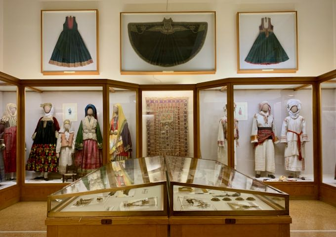 Traditional Greek garments on display in a museum