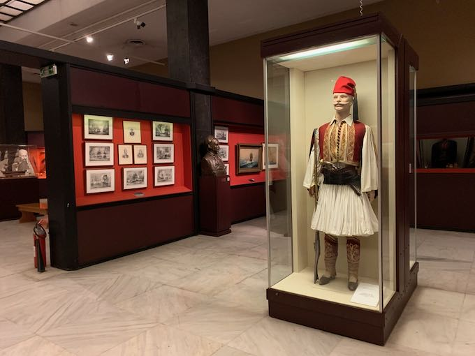Traditional Greek military attire is displayed in a museum