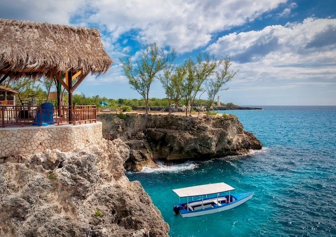 Tourists boat and lighthouse in Negril, Jamaica.