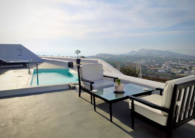 A dining table and a plunge pool overlooking the Santorini countryside