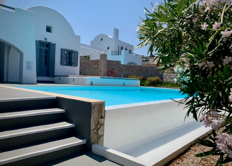 White hotel infinity pool backed by a Cycladic-style building