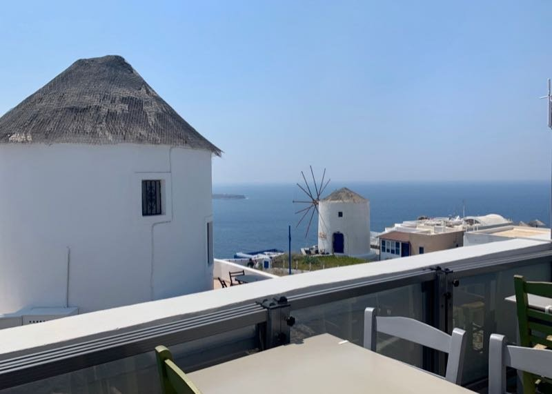 Windmill and ocean view at Rooftop patio with water view at Elinikon restaurant in Oia Santorini