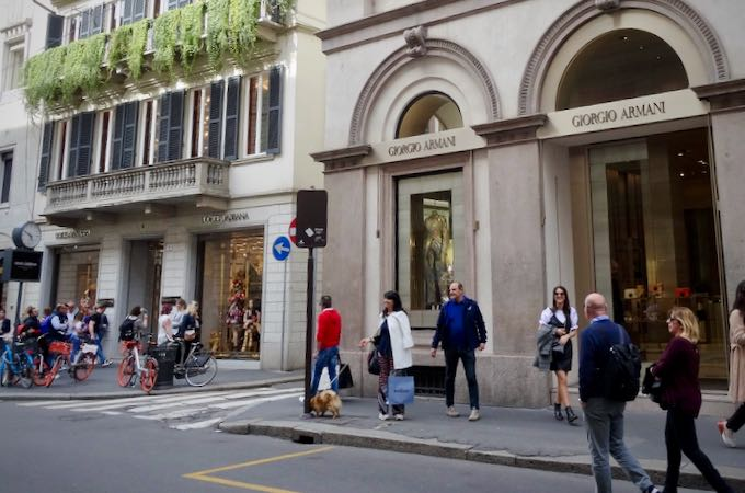 Shoppers walk by luxury clothing boutiques
