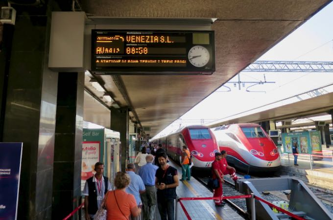 Boarding a train in Italy with ticket purchased in advance.