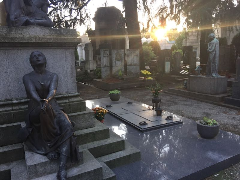 Bronze statues in a tree-lined cemetery