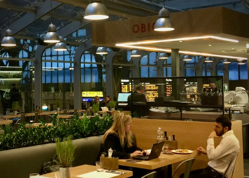 Two people share a meal and work at laptops in a high-end train station restaurant