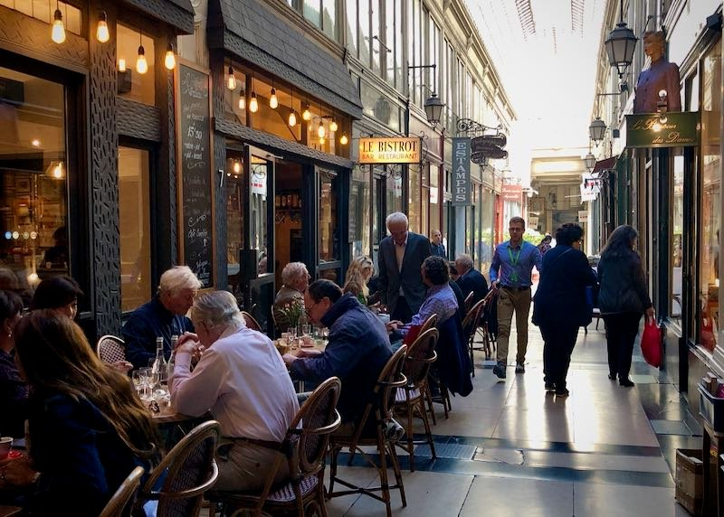Diners and shoppers in a covered shopping arcade in Paris