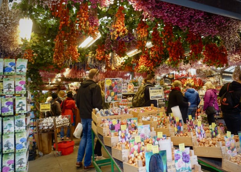Shoppers browse flowers and bulbs in a flower shop