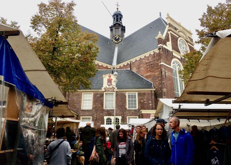 Bustling outdoor market beneath an old church spire