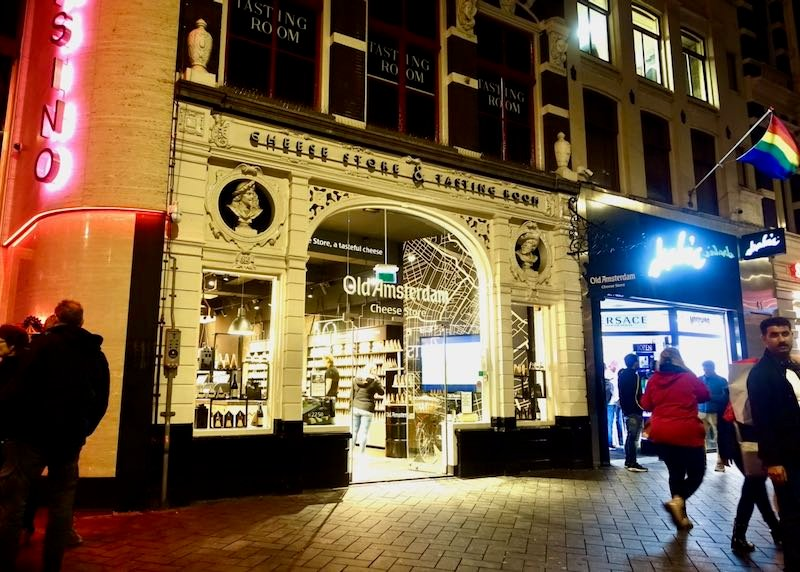 Exterior of a cheese shop in an old brick building at night