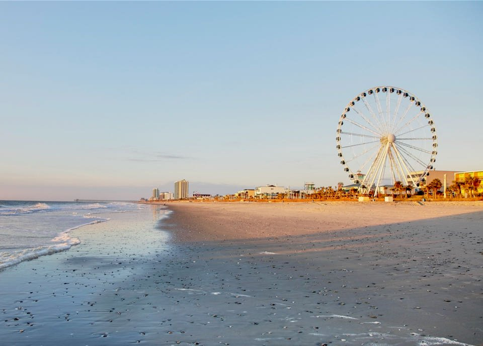Sandy becah with many buildings and a ferris wheel in the distance
