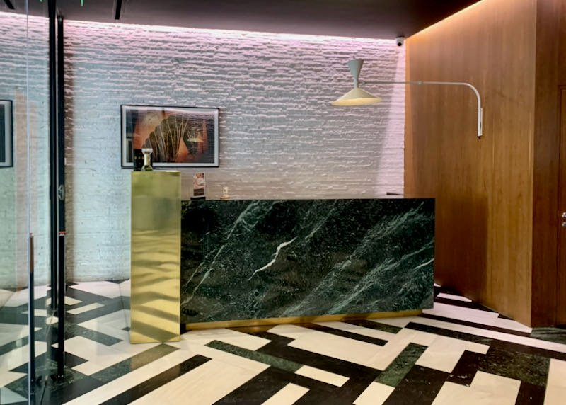 Green marble hotel reception desk on a black and white tiled floor.