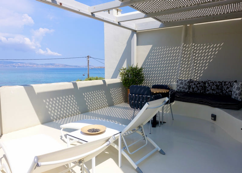 Balcony with lounge and dining chairs.