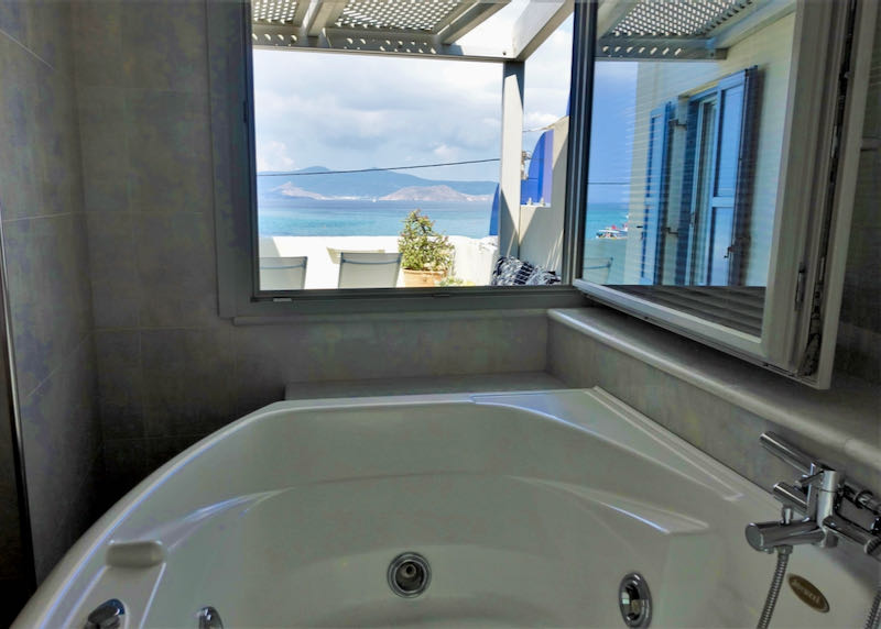 Jacuzzi tub next to a window opening to sea views.