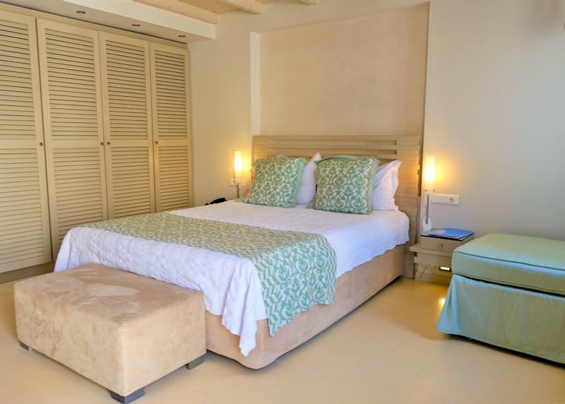 Hotel bed next to a wooden-slatted closet