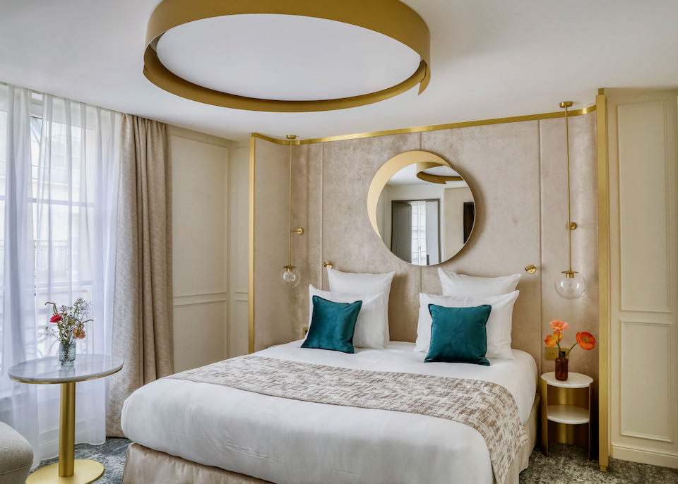 Hotel room with large comfortable looking bed, dressed in gold and teal hues