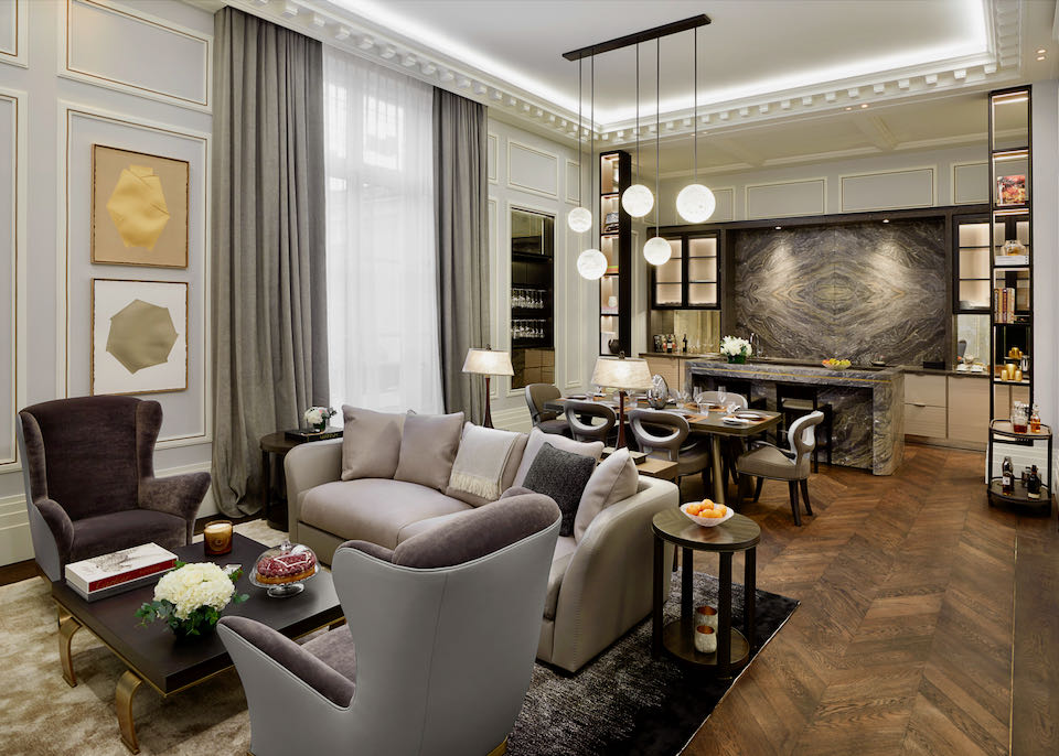 Hotel suite with velvet couch and side chairs, a kitchen and dining table, and statement chandelier