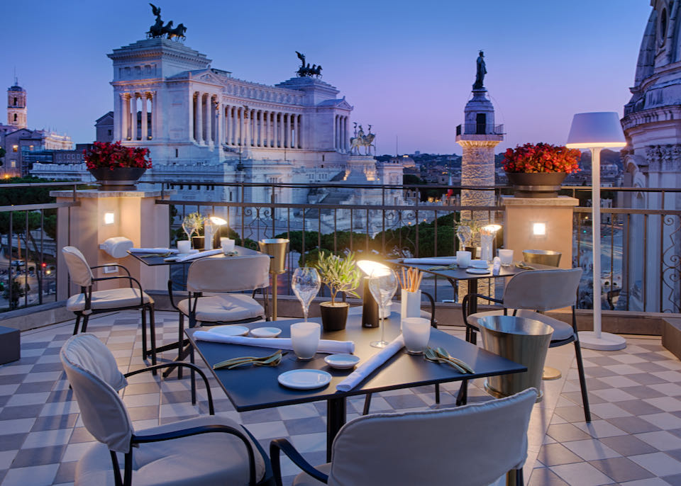Tables set for dinner on a rooftop patio with views over Rome at sunset
