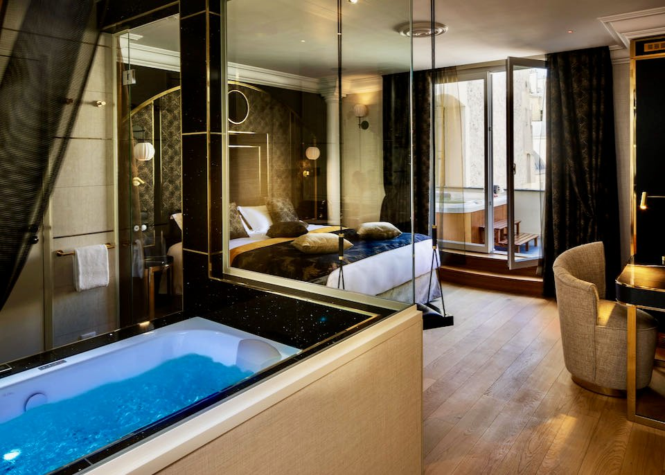 Hotel room with indoor and outdoor hot tubs, as well as a swing for adult use.