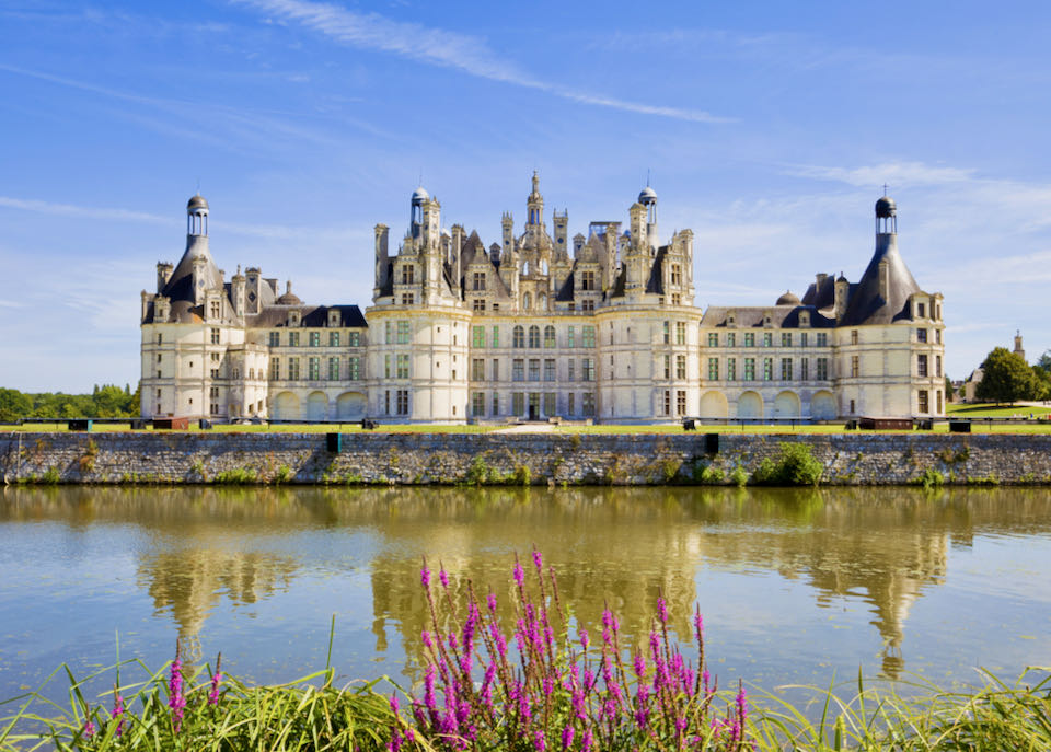 Great panoramic of Chambord Chateau reflected in the canal in a summer day with blue sky. There are some unrecognizable people in the balconies.