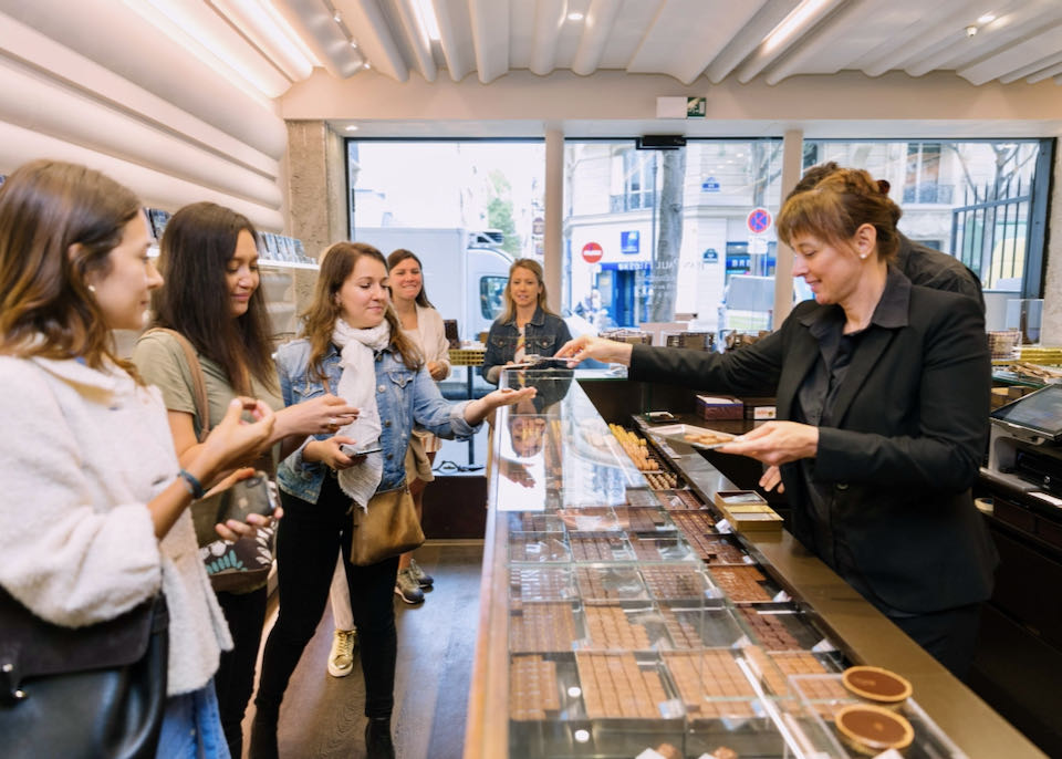 A woman behind the counter of a gourmet chocolate shop in Paris hands out samples to a group of patrons
