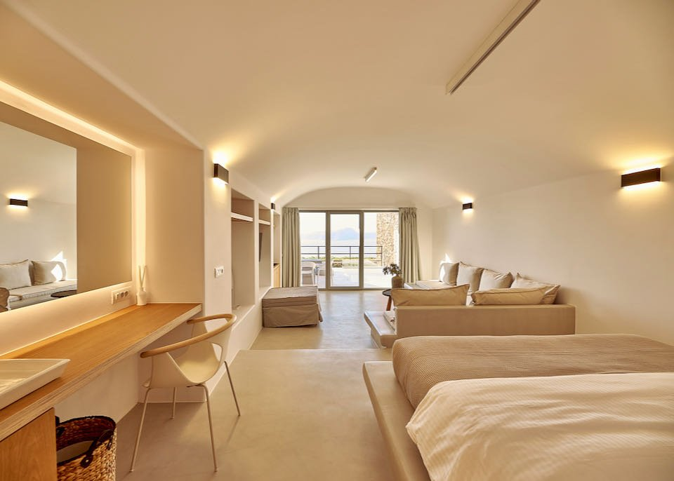 Cave-style hotel room with coved ceilings and soothing natural decor, with open doorway looking out to the sea