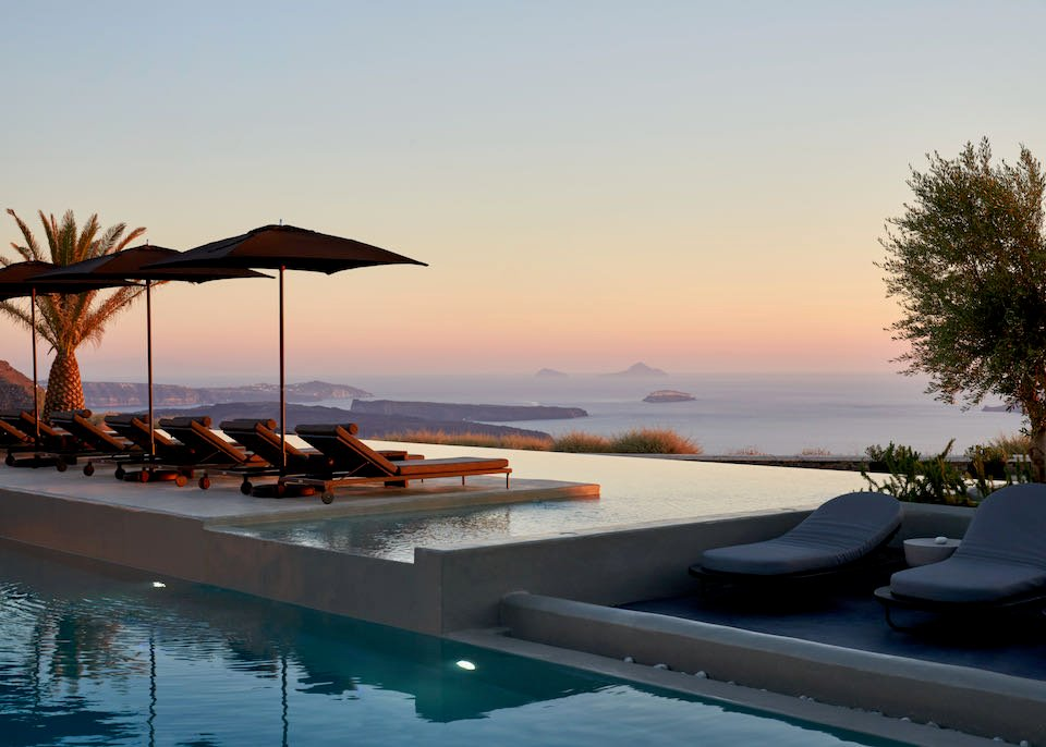 Overwater sun beds in a caldera-view infinity pool at sunset on Santorini