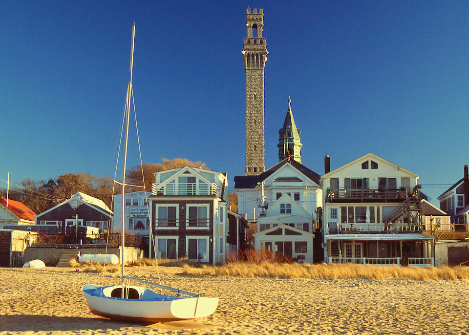 Looking inland from a sandy beach to a row of beachfront homes. A sailboat is sitting on the sand in the foreground.