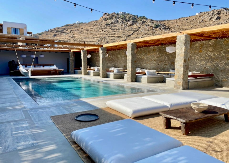 Pool deck surrounded by sun beds and wooden cabanas.