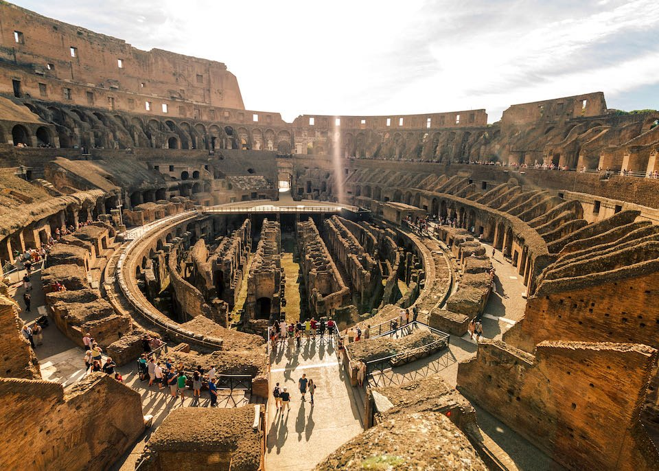 The Roman Colosseum as seen from above, with groups of tourists gathered around the edges.